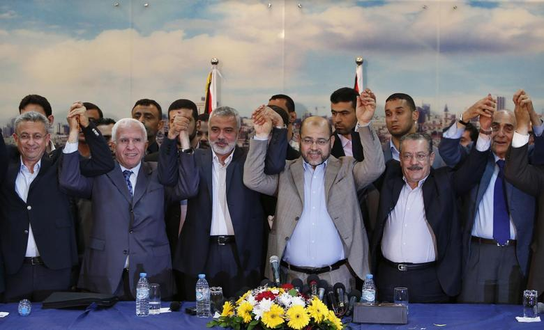Senior Fatah official Azzam Al-Ahmed (2nd L), head of the Hamas government Ismail Haniyeh (3rd L) and senior Hamas leader Moussa Abu Marzouq (4th L) , hold their hands after announcing a reconciliation agreement in Gaza City April 23, 2014. REUTERS/Suhaib Salem