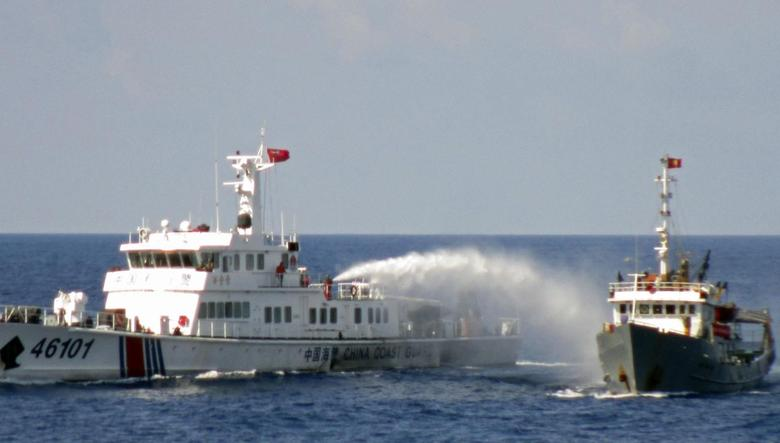 A Chinese coastguard vessel (L) uses water cannon on a Vietnamese Sea Guard ship on the South China Sea near the Paracels islands, in this handout photo taken on May 4, 2014 and released by Vietnam Marine Guard on May 8, 2014. REUTERS/Vietnam Marine Guard/Handout via Reuters