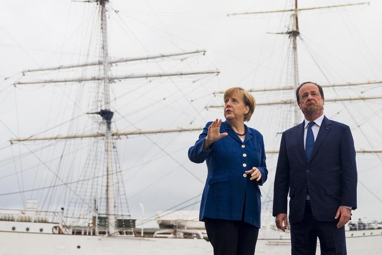 German Chancellor Angela Merkel (L) and French President Francois Hollande pose for pictures in front of the tall ship Gorch Fock I, in the northern city of Stralsund, May 10, 2014. REUTERS/Thomas Peter