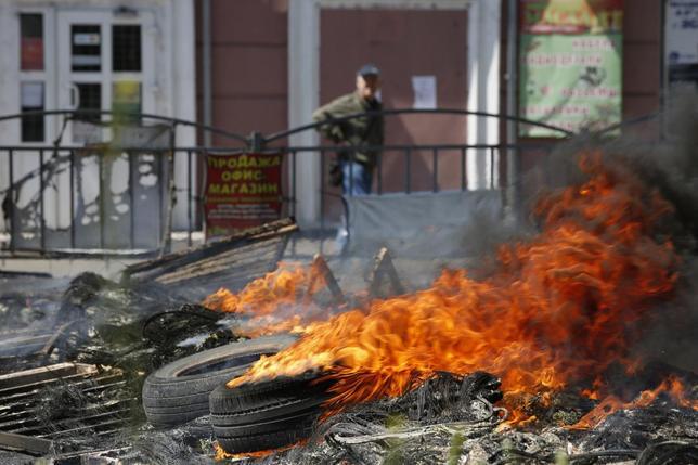 A man walks past a burning barricade near the city hall in Mariupol, eastern Ukraine May 10, 2014. REUTERS/Marko Djurica