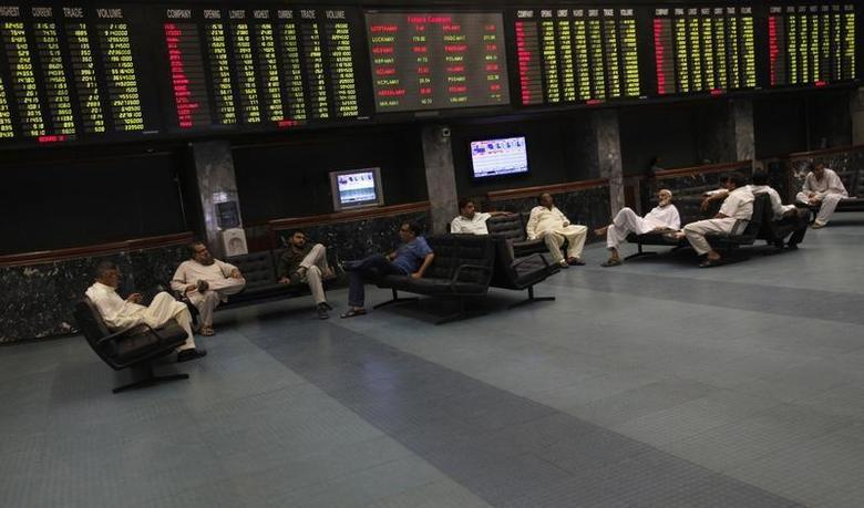 Traders sit underneath an electronic board displaying share prices during a trading session at the Karachi Stock Exchange May 13, 2013. REUTERS/Akhtar Soomro