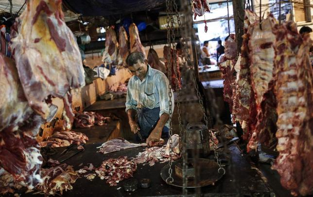 A butcher cuts up portions of beef for sale in an abattoir at a wholesale market in Mumbai May 11, 2014. REUTERS/Danish Siddiqui