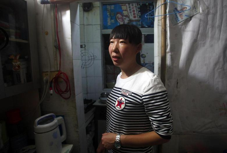 Wang Yafang stands inside her one-bedroom apartment in Shenzhen, Guangdong province April 17, 2014. REUTERS/John Ruwitch
