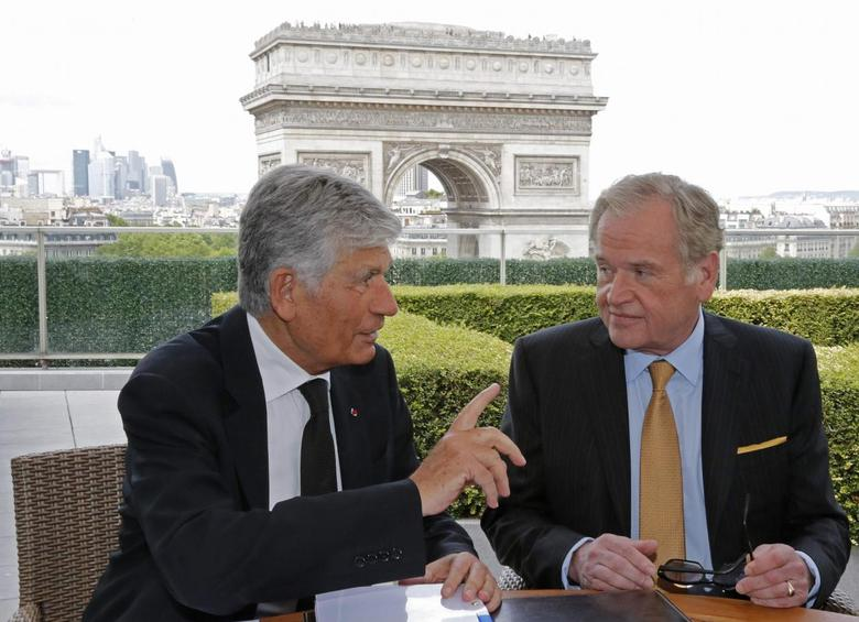 Maurice Levy (L), French advertising group Publicis Chief executive, and John Wren, head of Omnicom Group, gesture during a joint signature ceremony in Paris, in this July 28, 2013. REUTERS/Christian Hartmann