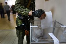 Вооруженный пророссийский ополченец опускает бюллетень в урну на избирательном участке в Славянске 11 мая 2014 года. Пророссийские сепаратисты объявили об уверенной победе на референдуме о государственной самостоятельности восточных областей Украины от Киева. REUTERS/Yannis Behrakis