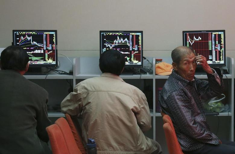 Investors sit in front of computer screens at a brokerage house in Shenyang, Liaoning province, May 12, 2014. REUTERS/Stringer