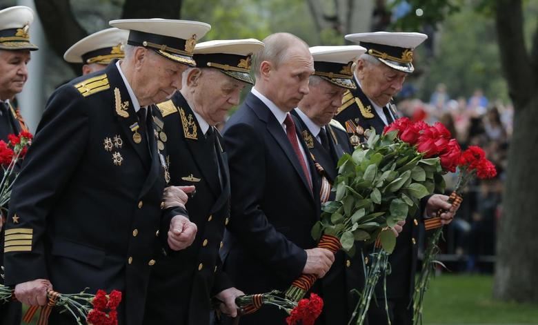 Russian President Vladimir Putin (C) stands with military personnel during a flower laying ceremony marking Victory Day in Sevastopol May 9, 2014. REUTERS/Maxim Shemetov