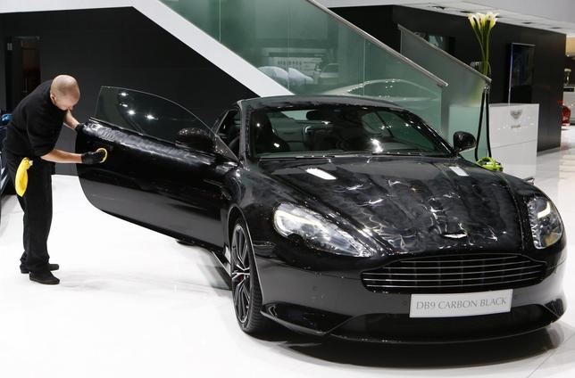 An employee applies wax to Aston Martin DB9 Coupe Carbon Black edition ahead of the 84th Geneva Motor Show at the Palexpo Arena in Geneva March 3, 2014. REUTERS/Arnd Wiegmann