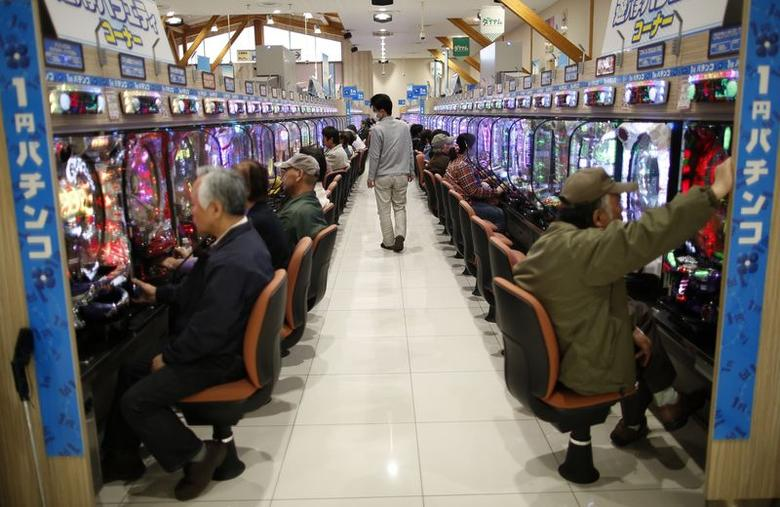 Visitors play Pachinko, a Japanese form of legal gambling, at Dynam Japan Holdings Co.'s Pachinko parlour in Koga, north of Tokyo April 7, 2014. REUTERS/Issei Kato/Files