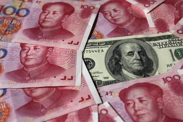 A U.S. $100 banknote is placed next to 100 yuan banknotes in this picture illustration taken in Beijing October 16, 2010. REUTERS/Petar Kujundzic