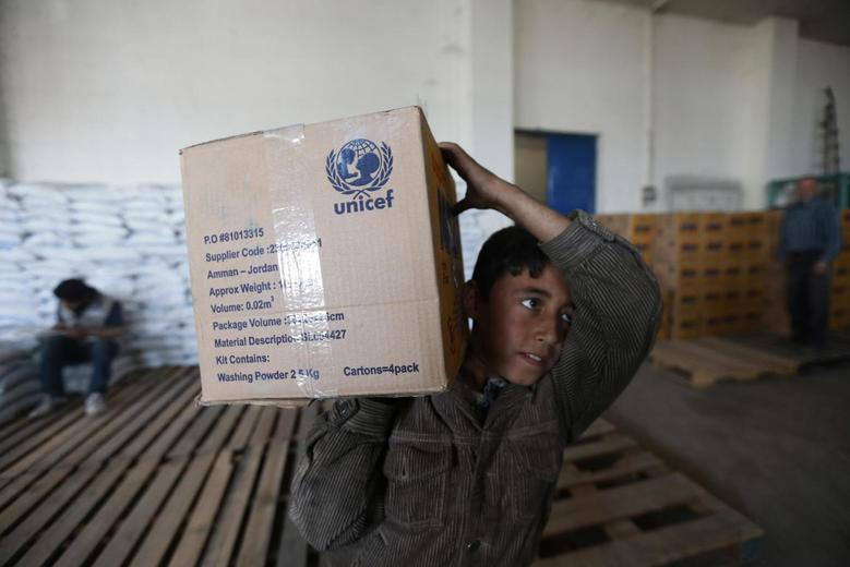 A boy receives humanitarian aid in Duma, Damascus March 29, 2014. REUTERS/Bassam Khabieh