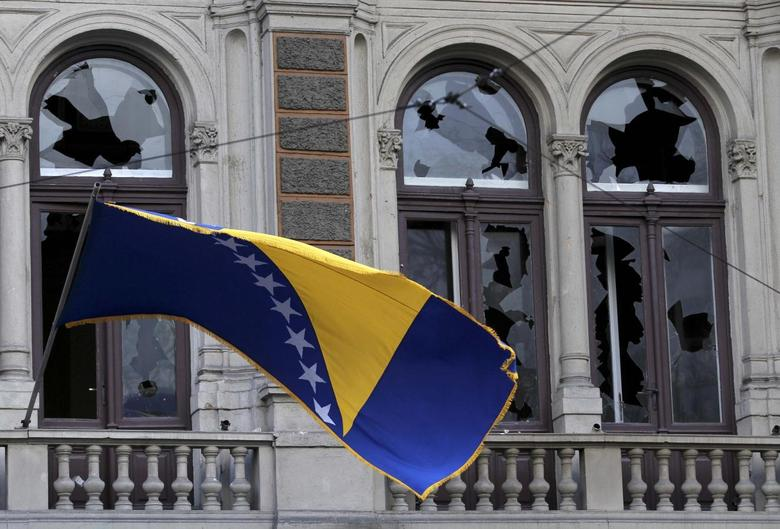 A Bosnian and Herzegovina national flag is seen on a damaged government building in Sarajevo February 8, 2014. REUTERS/Antonio Bronic