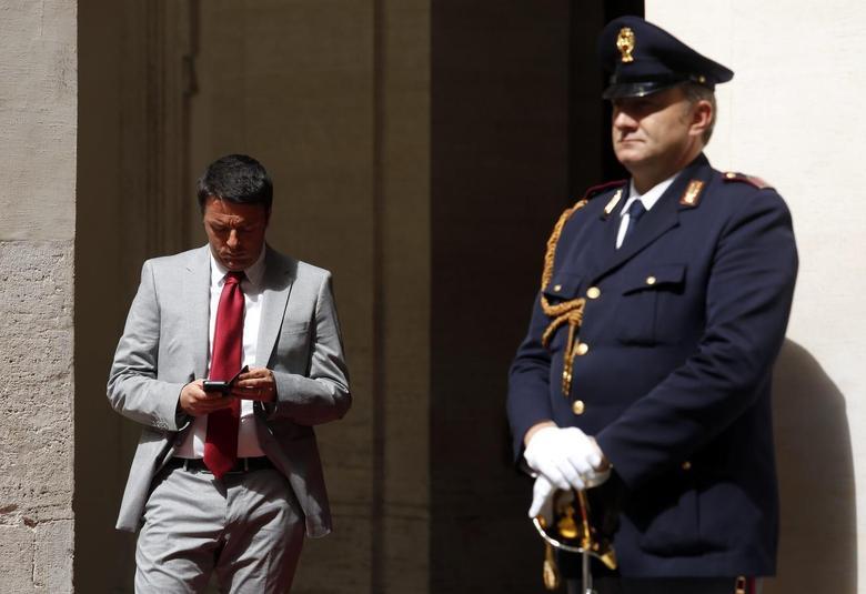 Italian Prime Minister Matteo Renzi checks his tablet before a meeting with U.N. Secretary General Ban Ki-moon at Chigi palace in Rome May 7, 2014. REUTERS/Remo Casilli