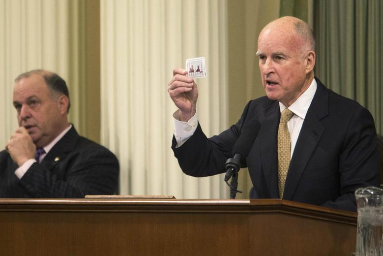 California Governor Jerry Brown holds a playing card detailing the state's fluctuating budgets during his State of the State address at the Capitol in Sacramento, California, January 22, 2014. REUTERS/Max Whittaker