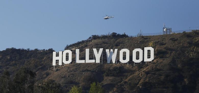 A Los Angeles Police Department (LAPD) helicopter flies over the Hollywood sign in Hollywood, California February 21, 2014. REUTERS/Mario Anzuoni