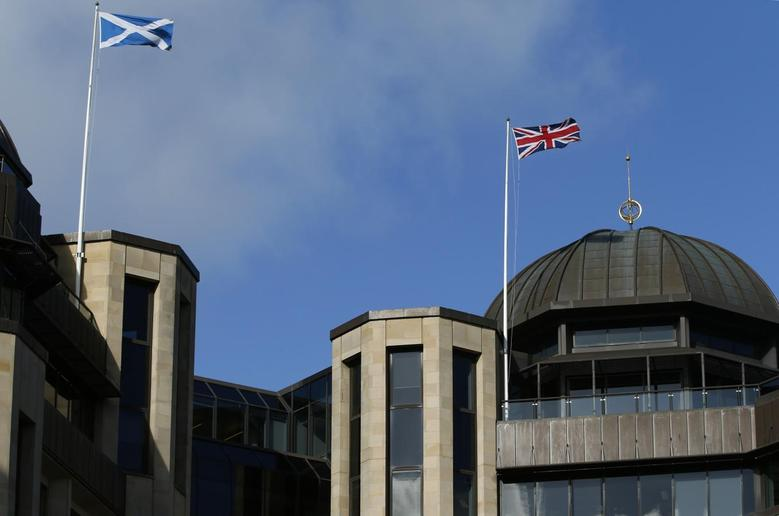 A Scottish Saltire flag (L) and a Union flag of the United Kingdom fly above Standard Life House in Edinburgh, Scotland February 27, 2014. REUTERS/Russell Cheyne