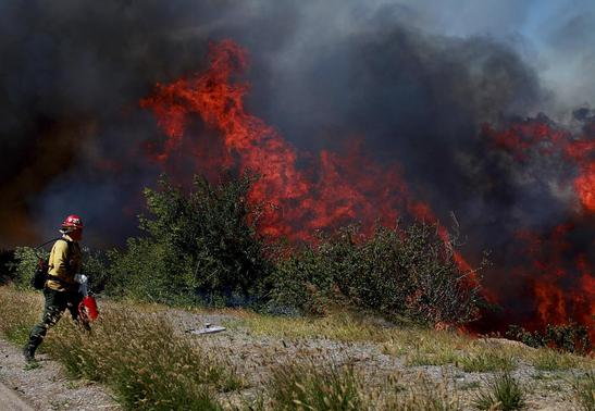 A firefighter battles the Ranch Fire near San Diego, California May 13, 2014. REUTERS/Sandy Huffaker