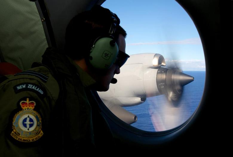 Flight Lieutenant Jamin Baker looks out an observation window aboard a Royal New Zealand Air Force (RNZAF) P3 Orion maritime search aircraft as it flies over the southern Indian Ocean looking for debris from missing Malaysian Airlines flight MH370 April 11, 2014. REUTERS/Richard Wainwright/Pool