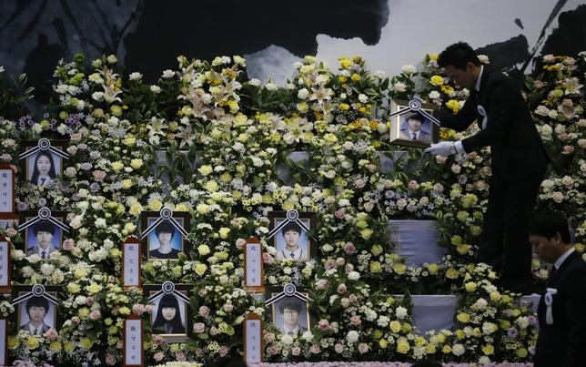 A funeral service employee puts up a portrait of victims of sunken passenger ship Sewol at the official memorial altar in Ansan May 2, 2014. REUTERS/Kim Hong-Ji