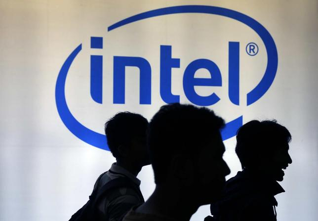 Indonesian youth walk past an Intel sign during Digital Imaging expo in Jakarta March 5, 2014. REUTERS/Beawiharta