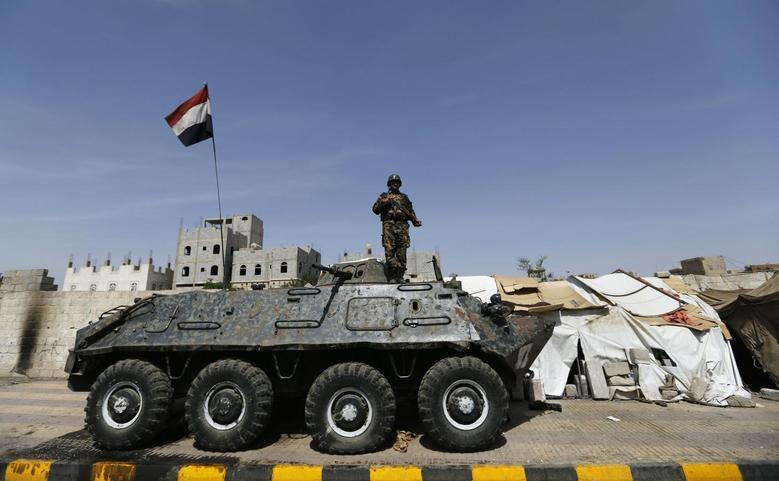 A police trooper stands on an armoured personnel carrier (APC) at a checkpoint in Sanaa May 14, 2014. REUTERS/Khaled Abdullah