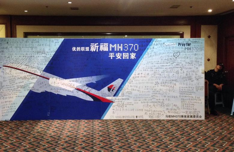 A policeman takes a nap beside a board written with messages for passengers onboard the missing Malaysia Airlines Flight MH370 during a closed meeting held between Malaysian representatives and Chinese relatives of passengers on Flight MH370 at Lido Hotel in Beijing May 2, 2014. REUTERS/Jason Lee