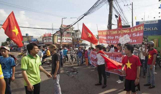 Workers wave Vietnamese national flags during a protest at an industrial zone in Binh Duong province May 14, 2014. REUTERS-Stringer