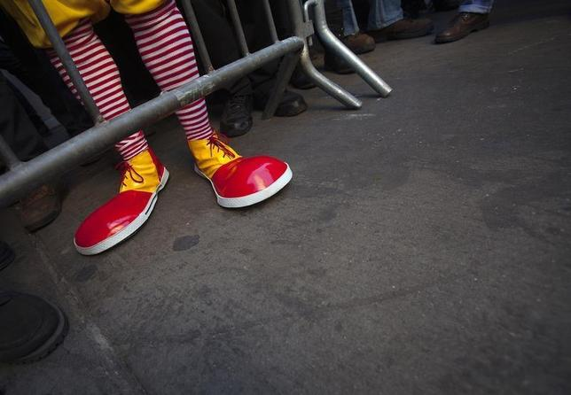 A protester Ben dressed up as Ronald McDonald, only known as Ben, takes part in a protest outside a McDonalds restaurant to demand higher wages for fast food workers in the Manhattan borough of New York March 18, 2014. REUTERS/Carlo Allegri
