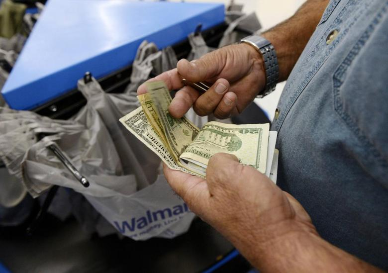 A customer counts his cash at the checkout lane of a Walmart store in the Porter Ranch section of Los Angeles November 26, 2013. REUTERS/Kevork Djansezian