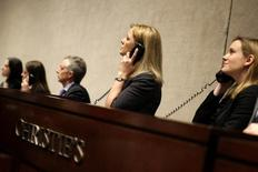Сотрудницы Christie's отвечают на звонки во время аукциона в Нью-Йорке 20 января 2012 года. Крупнейший в мире производитель алмазов в каратах - российская Алроса - начал сотрудничество с аукционным домом Christie's с продажи золотого кольца с бриллиантом за $847.000. REUTERS/ Kena Betancur
