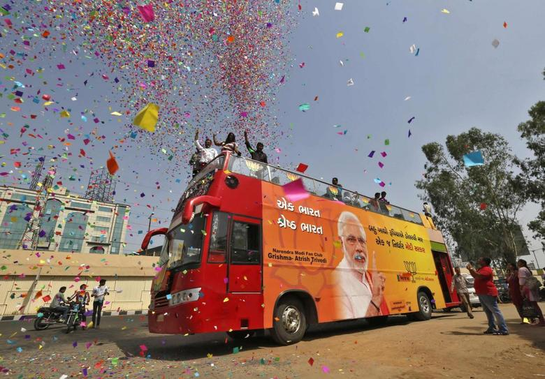 Supporters of Hindu nationalist Narendra Modi, the prime ministerial candidate for India's main opposition Bharatiya Janata Party (BJP), shower confetti from atop a bus in the western Indian city of Ahmedabad May 15, 2014. REUTERS/Amit Dave