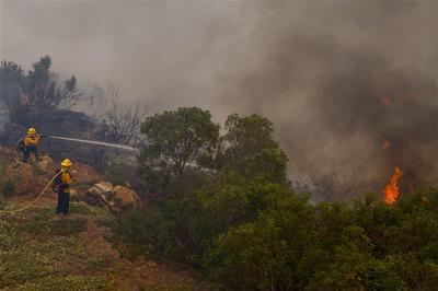 Wildfire races toward San Diego hillside suburb