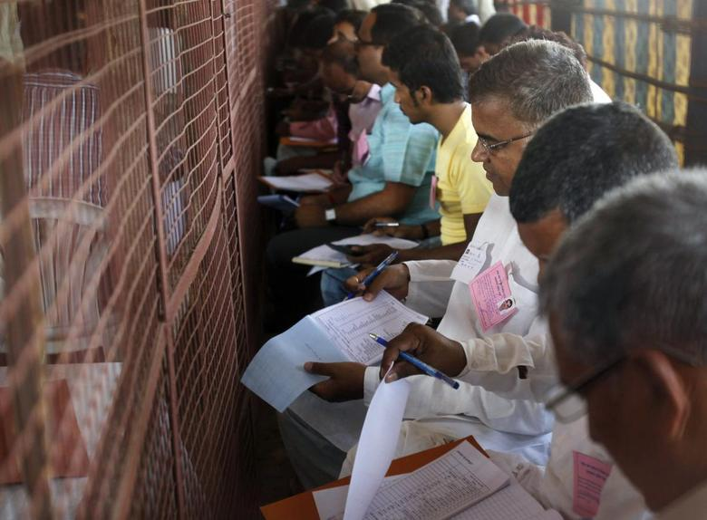 Voting agents from various political parties make notes as polling officials count votes at a counting centre in the northern Indian city of Allahabad May 16, 2014. REUTERS/Jitendra Prakash