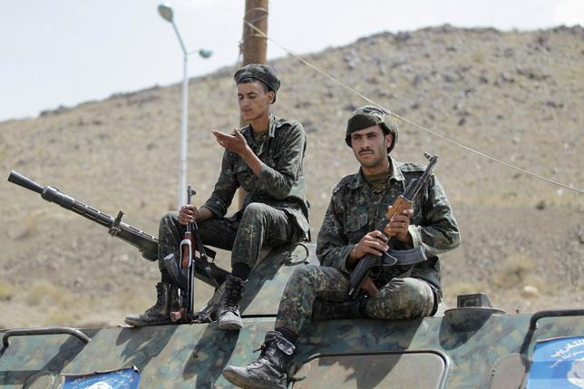 Police troopers sit as they guard atop an armoured personnel carrier (APC) at a checkpoint in Sanaa May 14, 2014. REUTERS/Khaled Abdullah