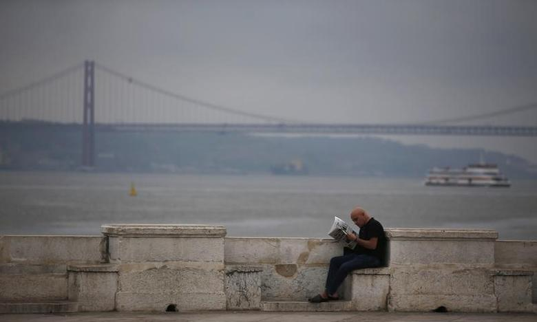 A man reads a newspaper at the Cais das Colunas, as a ship sails past, along the Tagus River in Lisbon July 11, 2013. REUTERS/Rafael Marchante