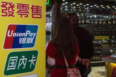 Chinese visitors walk past a sign for China UnionPay outside a pawnshop in Macau, in this November 20, 2013 file photo. REUTERS/Tyrone Siu/Files