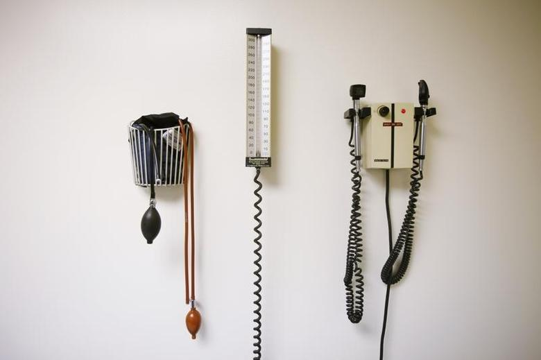Devices used to take blood pressure, temperature, and examine eyes and ears rest on a wall inside of a doctor's office in a file photo. REUTERS/Lucas Jackson