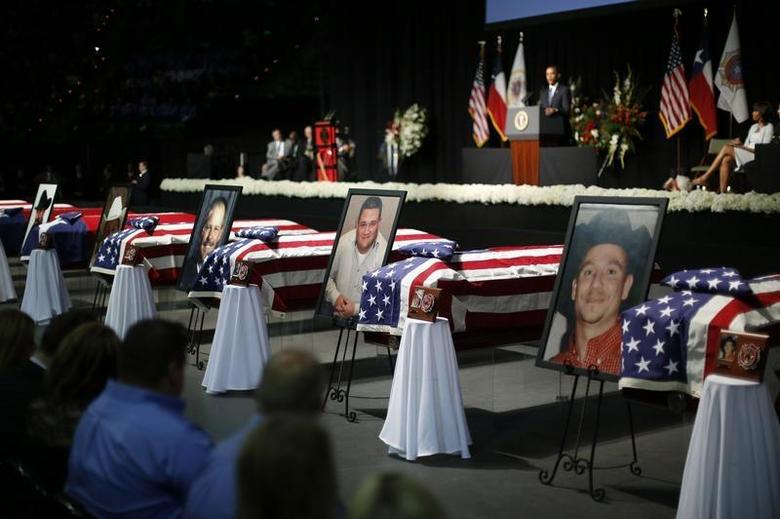 Portraits of twelve who died in the fertilizer plant explosion in West, Texas, are pictured alongside their coffins as U.S. President Barack Obama delivers remarks during a memorial ceremony held at Baylor University in Waco, Texas, April 25, 2013. REUTERS/Jason Reed