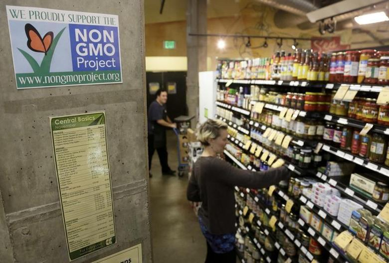 Employees stock shelves near a sign supporting non genetically modified organisms (GMO) at the Central Co-op in Seattle, Washington October 29, 2013. REUTERS/Jason Redmond