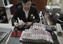 Una cajera cuenta fajos con billetes de 100 yuanes en una sede del banco China Merchants en Hefei, China, mar 17 2014. China está endureciendo su control sobre los préstamos interbancarios con normas más expansivas que incluyen limitar el volumen y el vencimiento de los créditos, a fin de ayudar a contener los riesgos en la banca informal y apoyar a la economía real. REUTERS/Stringer