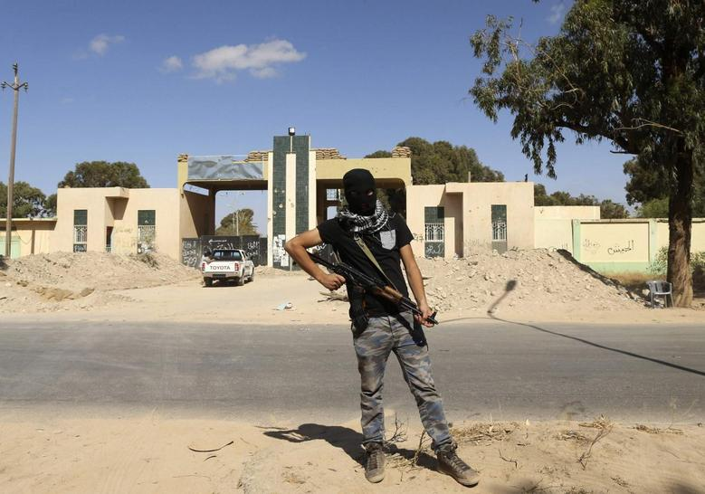 A militia stands guard in front of the entrance to the February 17 militia camp after Libyan irregular forces clashed with them in the eastern city of Benghazi May 16, 2014. REUTERS/Esam Omran Al-Fetori