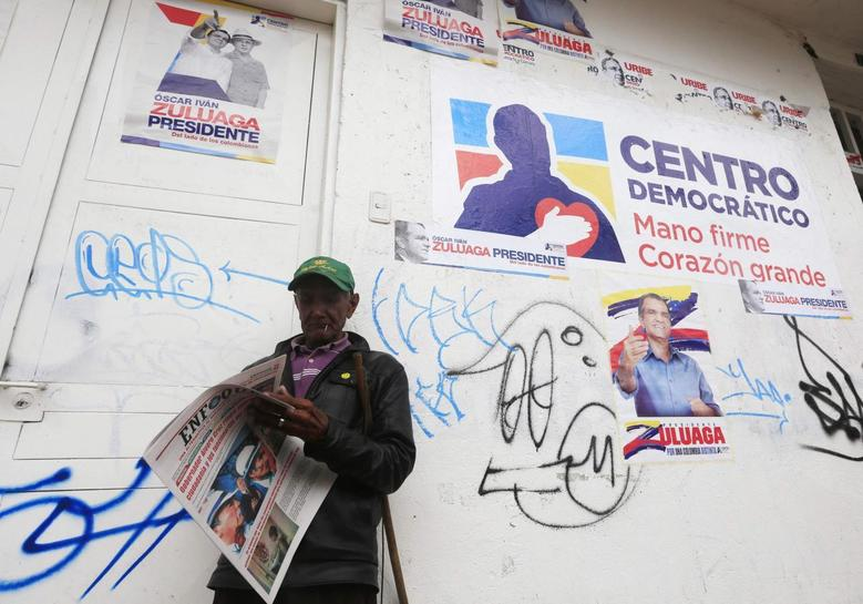 A citizen reads a newspaper in front of a campaign house of presidential candidate Oscar Zuluaga of the Centro Democratico party in Soacha May 12, 2014. REUTERS/Jose Miguel Gomez