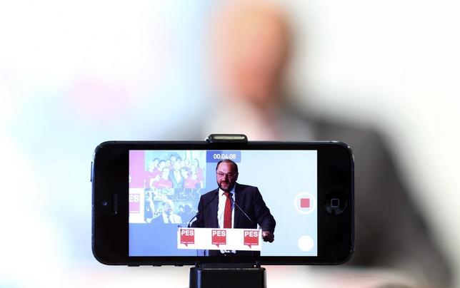 A journalist records the speech of Socialist candidate for European Commission president, Martin Schulz, with his mobile phone during a news conference in Brussels May 7, 2014. REUTERS/Francois Lenoir