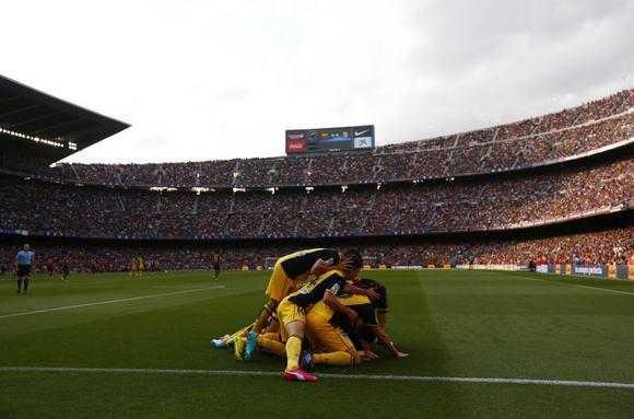 Atletico Madrid's Diego Godin (obscured) is congratulated by teammates after scoring against Barcelona during their Spanish first division soccer match at Camp Nou stadium in Barcelona May 17, 2014. REUTERS/Marcelo del Pozo