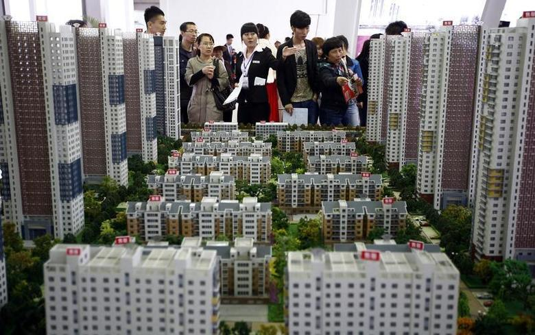 A sales assistant talks to visitors in front of models of apartments at a real estate exhibition in Shenyang, Liaoning province April 17, 2014. REUTERS/Stringer
