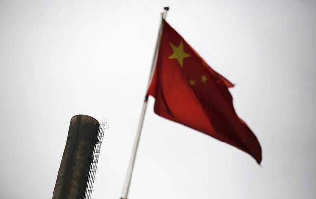 A Chinese national flag is seen in front of a chimney of a heat supply plant in Beijing May 13, 2014. REUTERS/Kim Kyung-Hoon