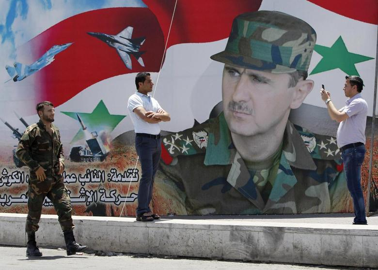 A man takes a photo of his friend in front of a poster of Syria's President Bashar al-Assad at Umayyad Square in Damascus May 16, 2014. REUTERS/Khaled al-Hariri