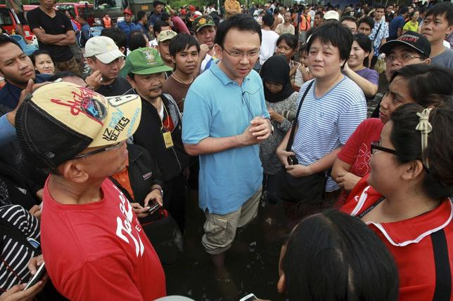 Basuki Tjahaja Purnama, Jakarta's then vice governor, talks to residents affected by floods during his visit to Jakarta January 19, 2013. REUTERS/Stringer