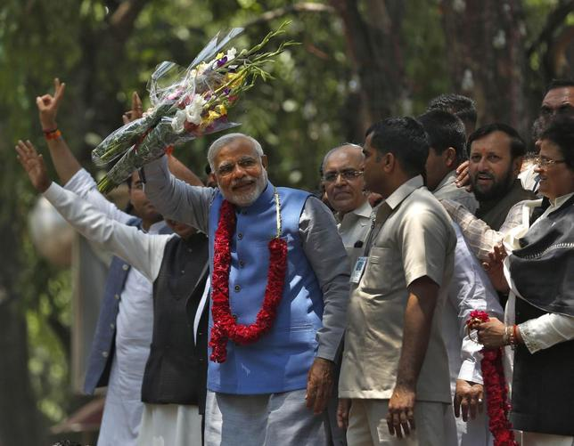 Hindu nationalist Narendra Modi (wearing a garland), the prime ministerial candidate for India's Bharatiya Janata Party (BJP), gestures to his supporters outside party's headquarters in New Delhi May 17, 2014. REUTERS/Ahmad Masood