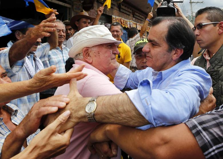Colombian presidential candidate Oscar Ivan Zuluaga (2nd R) embraces a supporter as he greets the crowd during a closing campaign rally in Villeta May 17, 2014. REUTERS/ John Vizcaino